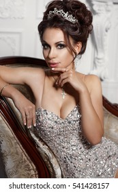 Gorgeous fashion woman in luxury evening dress with dark curly hair and bright makeup wears luxurious jewelry. Beauty model woman in lace dress with cristals in diamond crown studio portrait.