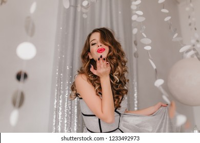 Gorgeous, fashionable curly dark-haired girl sends air kiss. Woman posing on background of silver shiny garlands