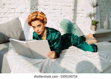 gorgeous fashionable woman in silk pajamas with hair curlers reading book, lying in bed