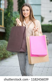 Gorgeous fashionable young brunette woman outdoors with shopping bags.