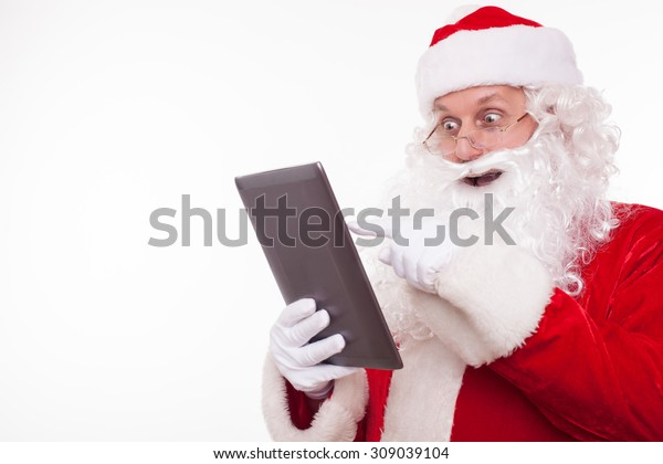 Gorgeous Father Christmas is using a laptop with pleasure. He is looking at it with surprise and laughing. Isolated on background and copy space in left side