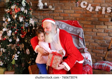 Gorgeous female child with great joy presents box Christmas surprise to Santa Claus who sits on large and soft armchair in cozy spacious room decorated for New Years holidays floor lamp, walls which