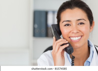 Gorgeous female doctor on the phone and posing in her office