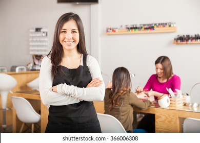 Gorgeous female Latin business owner standing in front of her nail salon while a customer gets a manicure