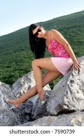Gorgeous female in miniskirt sitting on rocks