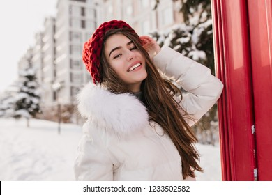 Gorgeous female model with straight hairstyle posing on snowy street in good mood. Outdoor photo of glad pale woman in knitted red hat having fun during winter photoshoot before christmas.
