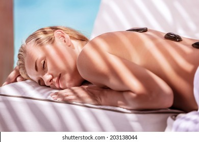 Gorgeous female spending summer vacation on luxury spa resort, massage procedure with black hot stones on the beach