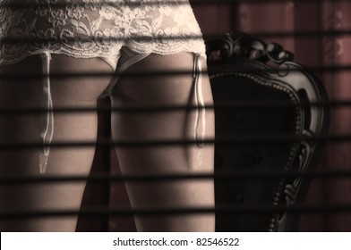 Gorgeous female standing in lingerie behind blinds