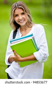 Gorgeous female student holding notebooks outdoors