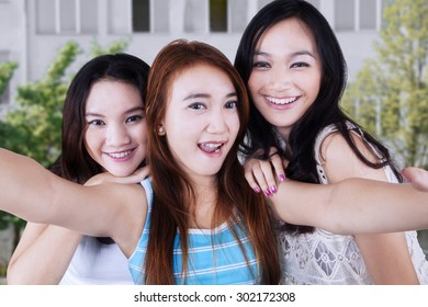 Gorgeous female students taking self picture together at school yard