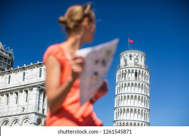 Gorgeous female tourist with map admiring the Leaning Tower of Pisa, Tuscany, Italy (shallow DOF)