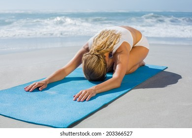 Gorgeous fit blonde in childs pose on the beach on a sunny day