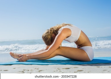 Gorgeous fit blonde in seated forward bend pose on the beach on a sunny day