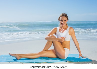 Gorgeous fit blonde in seated yoga pose on the beach on a sunny day