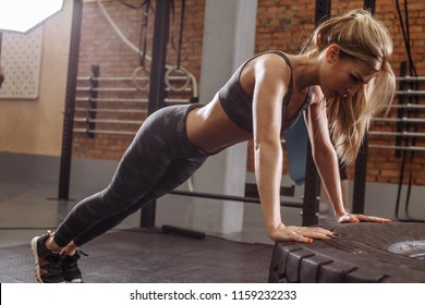 gorgeous fit girl is raising the body during the push-up workout. athletic training.