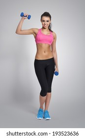 Gorgeous fitness instructor with dumbbells