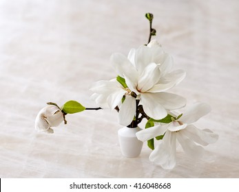 A gorgeous floral arrangement of fresh white magnolia blossoms in a miniature ceramic vase on natural white quartzite