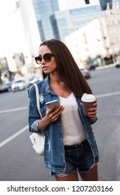 Gorgeous and funky. Beautiful young woman in jeans jacket holding coffee cup and looking away while standing outdoors