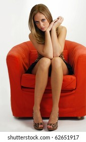gorgeous girl with beautiful legs sitting on a red sofa