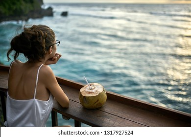 Gorgeous girl in black glasses and a white blouse sits in the outdoor cafe by the wooden rack and looks at the sunset over the sea on Bali. There is a coconut with a white straw near her. Horizontal.