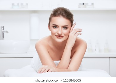 Gorgeous girl with brown hair fixed behind, clean fresh skin, big eyes and naked shoulders posing at spa cabinet background, wearing white towel and smiling.