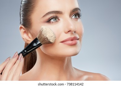 Gorgeous girl with brown hair fixed behind, clean fresh skin, big eyes and naked shoulders posing at gray studio background, beauty photo, using make up brush with powder.