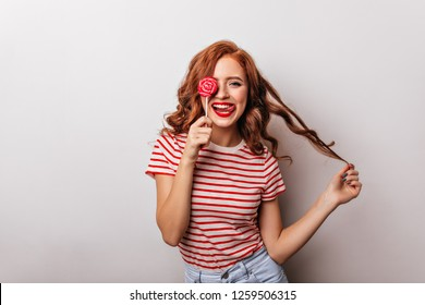 Gorgeous girl with candy playing with her curly hair. Studio photo of graceful long-haired lady with lollipop.