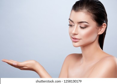 Gorgeous girl with dark wet hair and nude make up and naked shoulders at studio background, SPA concept, close up portrait, holding product.