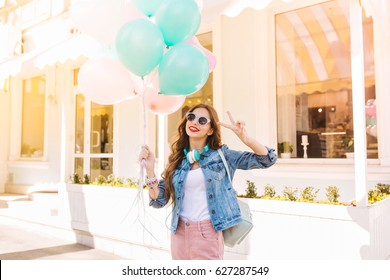 Gorgeous girl with long hair wearing denim jacket and pink skinny jeans posing, while having fun on party. Charming young woman in glasses with retro outfit holding balloons and celebrating birthday