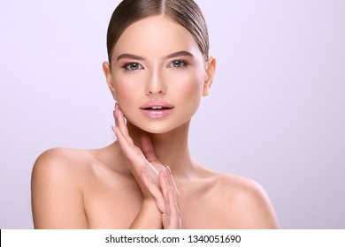 Gorgeous girl with naked shoulders, fixed hair and nude make up posing at white background, make up tutorial.