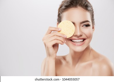 Gorgeous girl with nude make up and naked shoulders posing at grey background with cleaning sponge, skin care concept, beauty photo, smiling.