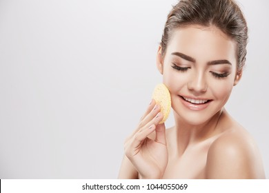 Gorgeous girl with nude make up and naked shoulders posing at grey background with cleaning sponge, skin care concept, beauty photo.
