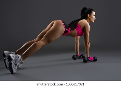 Gorgeous girl in pink sportswear doing fitness with dumbells shot