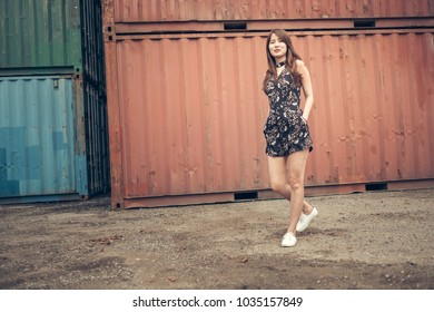 Gorgeous girl stroll beside freight shipping containers.