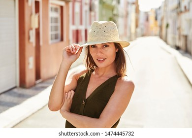 Gorgeous girl in sunhat, smiling from street to camera