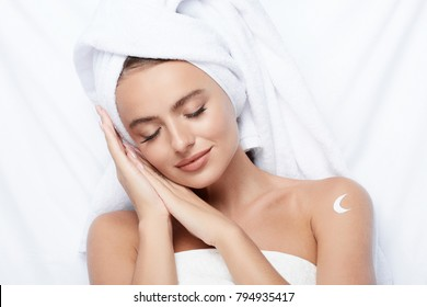 Gorgeous girl with thick eyebrows and perfect skin at white background, towel on head, beauty photo concept, skin care, spa concept, using cream, sleeping, night cream.