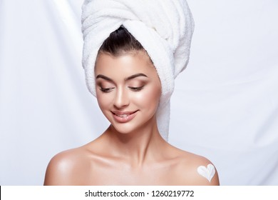 Gorgeous girl wearing white towel at white studio background, beauty photo concept, close up, SPA, health care concept, using body cream.