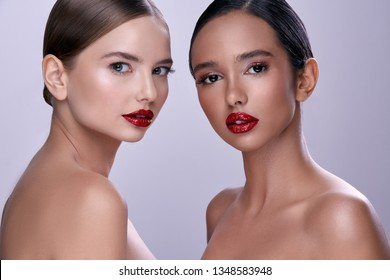Gorgeous girls wearing evening make up with naked shoulders posing at gray background.