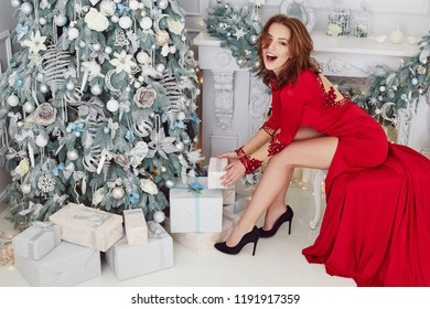Gorgeous glamour women in a long red evening dress sitting in a chair near the decorative fire place. Beautiful New Year and Christmas scene, Beauty Fashion Model holding christmas gift.