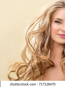 Gorgeous Hair. Beauty Fashion Model Woman with Long and Healthy  Hair. Blonde Girl with long curly hair smiling. Professional Makeup.