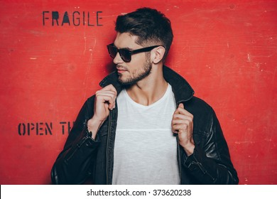 Gorgeous and handsome. Handsome young man in sunglasses adjusting his jacket and looking away while standing against red background