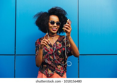 Gorgeous happy afro american young woman in sunglasses, dancing while listening to music in headset on her phone. Dressed in vivid blouse, with short curly hairstyle. Outdoors.