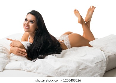 Gorgeous happy brunette in bed on her stomach view