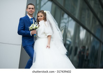 gorgeous happy brunette bride and elegant groom in blue suit with bouquet on the background of modern building