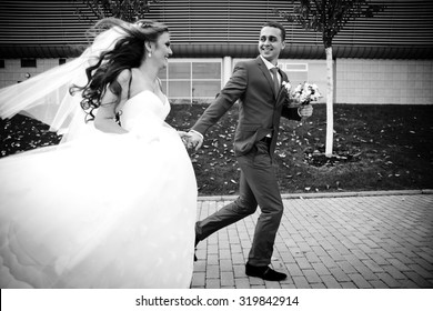 gorgeous happy brunette bride and elegant groom in blue suit running on the background of modern building and autumn trees