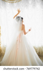 Gorgeous happy luxury brunette bride near a window on the background of vintage room