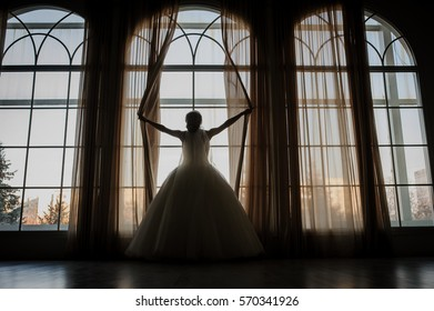 gorgeous happy luxury stylish bride near a window holding curtains in vintage studio room