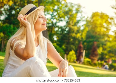 Gorgeous happy mature woman sitting on the grass relaxing at the local park adjusting her hat smiling looking away dreamily copyspace lifestyle people maturity dreaming emotions beauty fashion weekend