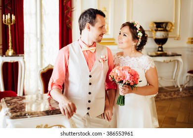 Gorgeous happy stylish couple lovely hugging on the background of luxurious interior of the amazing castle. Pink colors