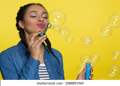 Gorgeous happy young African woman blowing bubbles on yellow background copy space. Cheerful and carefree female having fun expressing joy and harmony